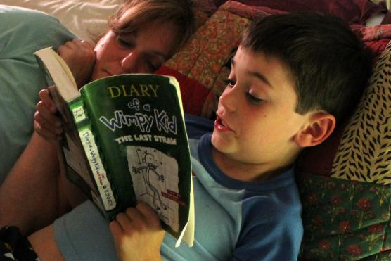 A child reads a book with his mother
